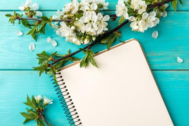 Ramos de cerejeira em flor de primavera e caderno sobre fundo azul de madeira.