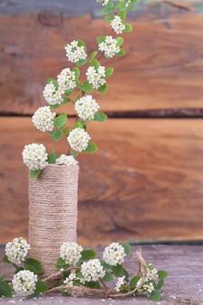 Ramos de floração em um vaso em uma textura de madeira. estilo japonês wabi sabi. decoração de casa