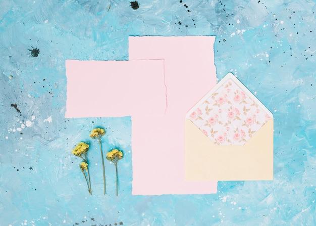 Ramos de flores amarelas com envelope aberto na mesa azul