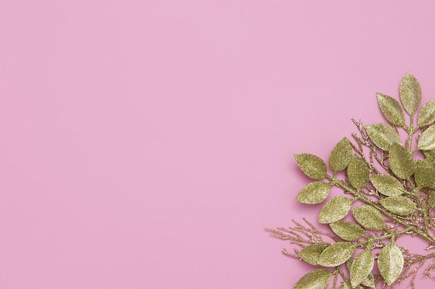 Ramos de glitter dourado floral na mesa rosa com espaço de cópia