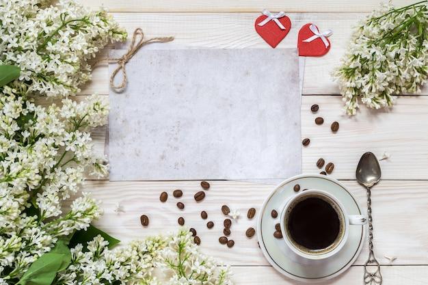 Ramos de lilás, dois corações e café em uma xícara em um fundo de madeira. lugar para o texto.