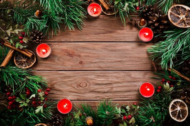 Ramos de natal com velas na mesa de madeira