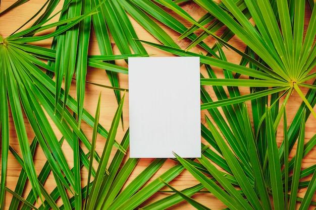 Ramos de palmeira verde em cima da mesa de madeira. cartão ecológico com folhas de palmeira e papel branco no centro para texto.
