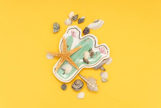 Ramos de palmeiras com estrela do mar e conchas sobre fundo amarelo