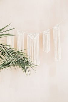 Ramos de palmeiras tropicais exóticas e decoração no estilo boho em fundo bege claro