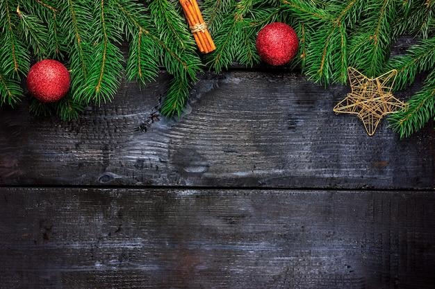 Ramos de pinheiro com paus de canela e bolas de natal em uma árvore preta vista de cima da moldura decorativa