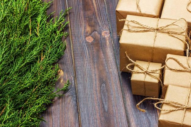 Ramos de pinheiro de natal com caixa de presente no escuro de madeira rústica