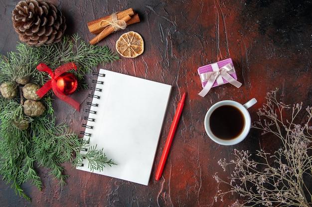 Ramos de pinheiro e caderno espiral fechado com cone de conífera de lima e canela e uma xícara de chá preto em fundo escuro