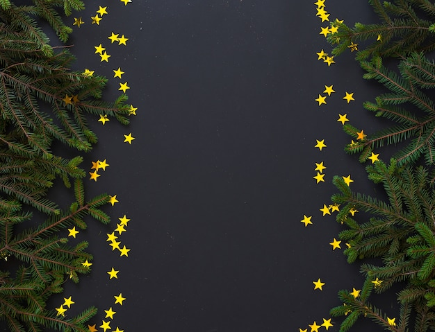 Ramos de pinheiro e estrelas douradas na superfície preta