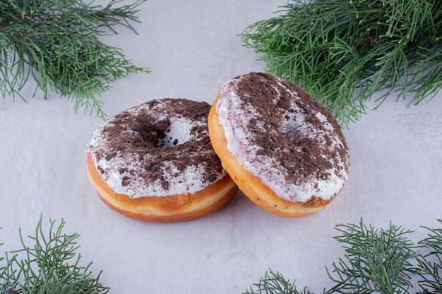 Ramos de pinheiro em torno de dois donuts em fundo branco.