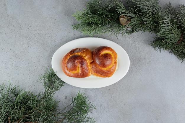 Ramos de pinho natural atrás de uma bandeja de pão doce na mesa de mármore.