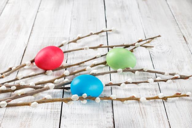 Ramos de salgueiro e ovos de páscoa pintados em uma mesa de madeira natural branca. estilo rústico