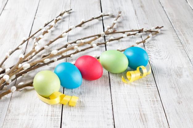 Ramos de salgueiro e ovos de páscoa tingidos brilhantes