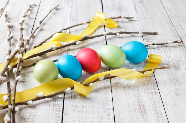Ramos de salgueiro e ovos de páscoa tingidos em uma mesa de madeira branca natural com uma fita amarela brilhante. estilo rústico