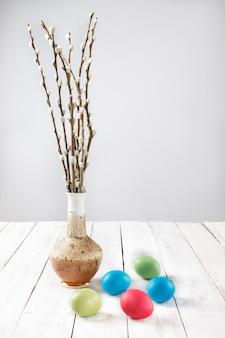 Ramos de salgueiros em um vaso e ovos de páscoa tingidos em uma mesa de madeira branca.