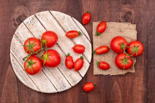 Ramos de tomate cereja na placa de madeira perto dos tomates de saco em madeira