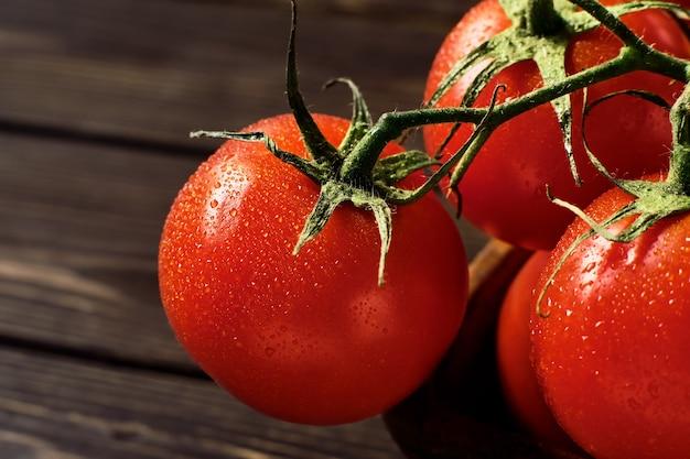 Ramos de tomates vermelhos suculentos maduros em uma mesa de madeira escura