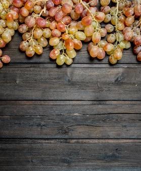 Ramos de uvas-de-rosa. sobre um fundo de madeira.