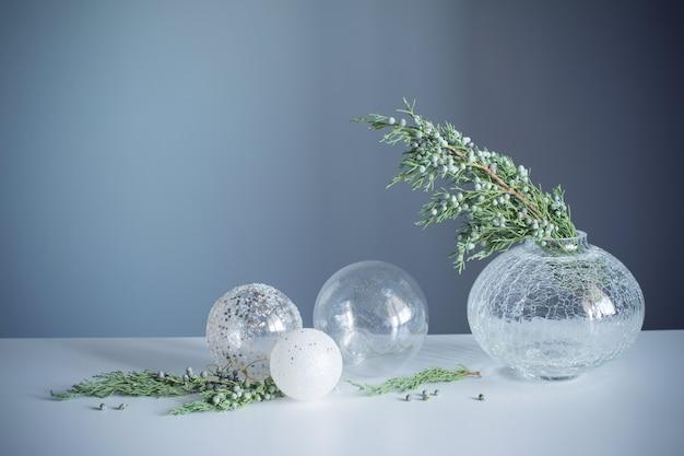 Ramos de zimbro em vaso de vidro e bolas de natal em fundo cinza