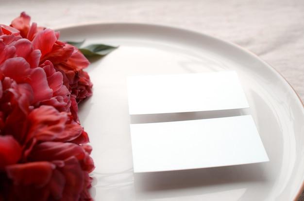 Ramos desabrochando com flores e botões de peônia maquete de cartão de visita em branco na placa de cerâmica