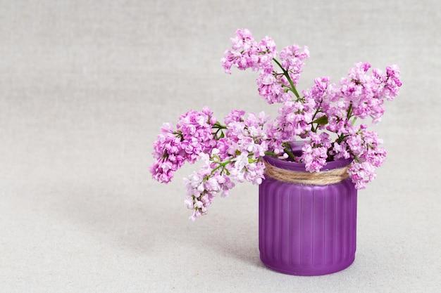 Ramos do lilás cor-de-rosa de florescência no vaso no fundo borrado de pano com espaço da cópia.