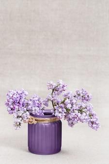 Ramos do lilás de florescência com o vaso no fundo borrado com espaço da cópia.