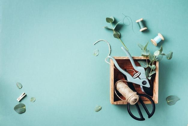 Ramos e folhas de eucalipto, podador de jardim, tesoura, caixas de madeira