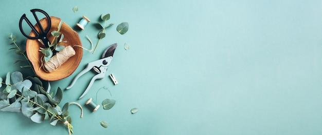 Ramos e folhas de eucalipto, podador de jardim, tesoura, placa de madeira