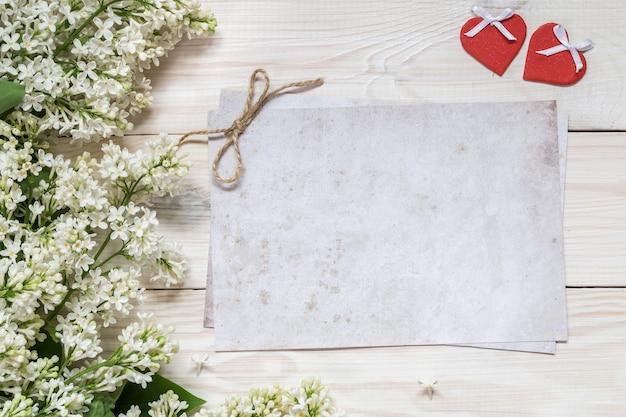 Ramos lilás e dois corações em um fundo de madeira. lugar para o texto.