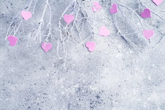 Ramos na neve com corações rosa em um fundo de concreto