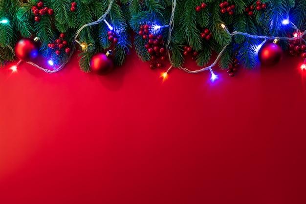 Ramos spruce de natal e bagas vermelhas sobre fundo vermelho.