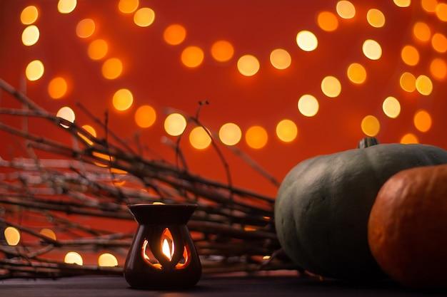 Ramos, velas e abóboras em um fundo laranja com bokeh. dia das bruxas. copie o espaço.