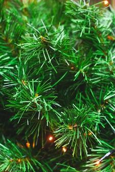 Ramos verdes do fundo não natural da árvore de natal do plástico.