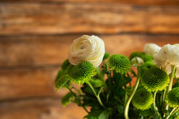 Ranunculi branco e flores verdes da mola no fundo de madeira.