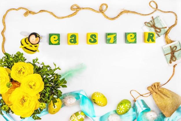 Ranúnculo botões de ouro, abelha decorativa, ovos pintados de páscoa com penas, bolsa de lona com presentes.