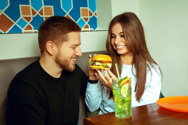 Rapariga a alimentar o seu namorado com hambúrguer