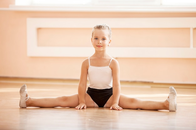 Rapariga a fazer splits enquanto se aquece na aula de ballet