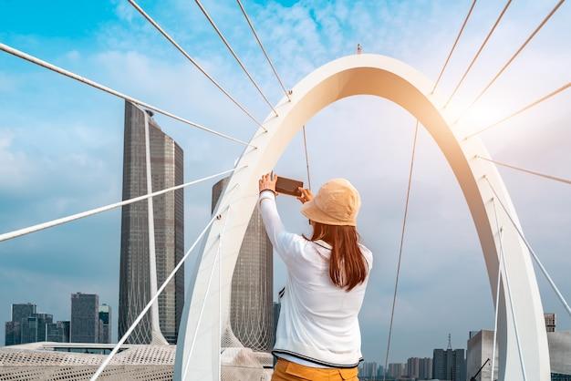 Rapariga a tirar uma fotografia e o horizonte de um edifício moderno em nanjing