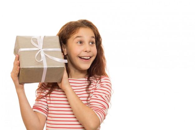 Rapariga adorável com um presente de natal