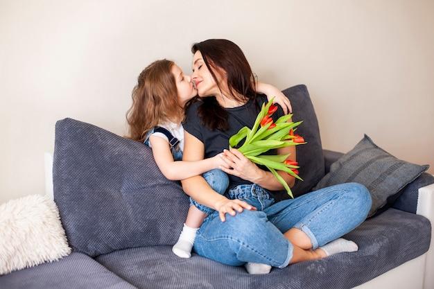 Rapariga adorável que abraça sua mãe bonita