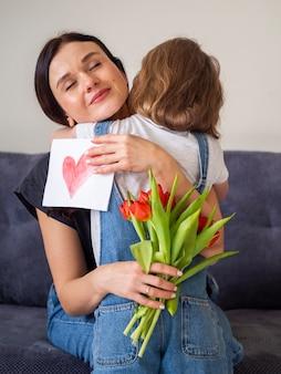 Rapariga adorável que abraça sua mãe