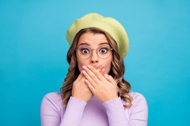 Rapariga atônita contando uma novidade privada impressionada com a boca fechada na parede azul