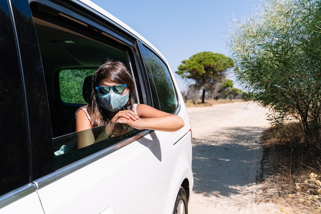 Rapariga baixa com cabelo castanho, máscara facial e óculos de sol a espreitar pela janela do carro a sair de férias numa estrada de pinheiros no meio da covidida 19 pandemia de coronavírus