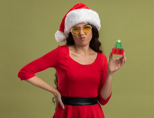 Rapariga bonita com a testa franzida, usando chapéu de papai noel e óculos, segurando o brinquedo da árvore de natal com data mantendo a mão na cintura isolada na parede verde oliva