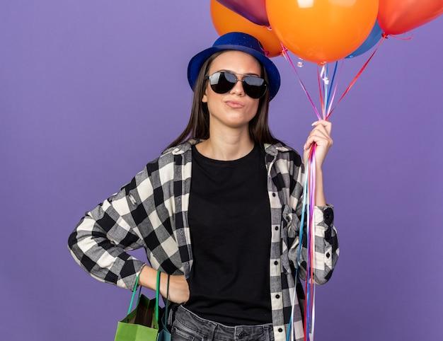 Rapariga bonita com chapéu de festa e óculos segurando balões e colocando a mão no quadril