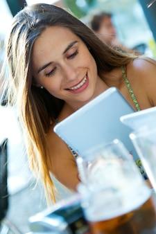 Rapariga bonita com sua tabuleta digital.