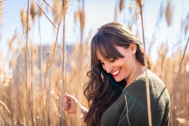 Rapariga bonita no campo e sentindo a natureza
