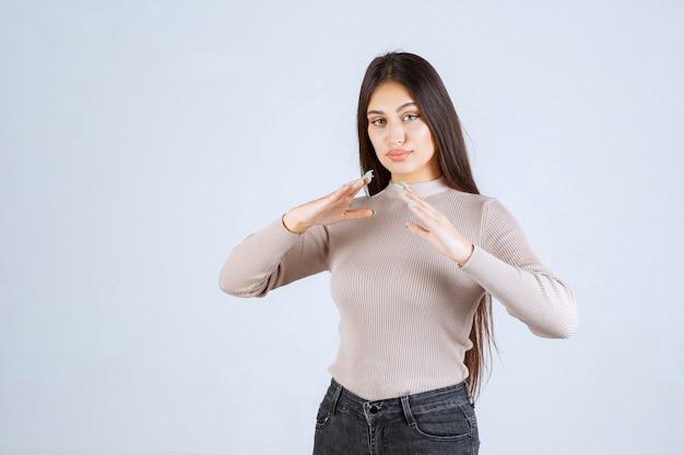 Rapariga com camisola cinzenta, mostrando as dimensões de um objeto.