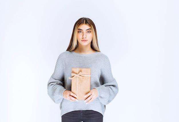 Rapariga com camisola cinzenta, segurando uma caixa de presente de papelão.