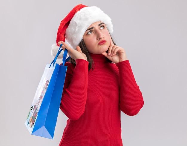 Rapariga com camisola vermelha e chapéu de pai natal a segurar num saco de papel colorido com presentes de natal a olhar para cima com expressão pensativa a pensar em pé sobre um fundo branco